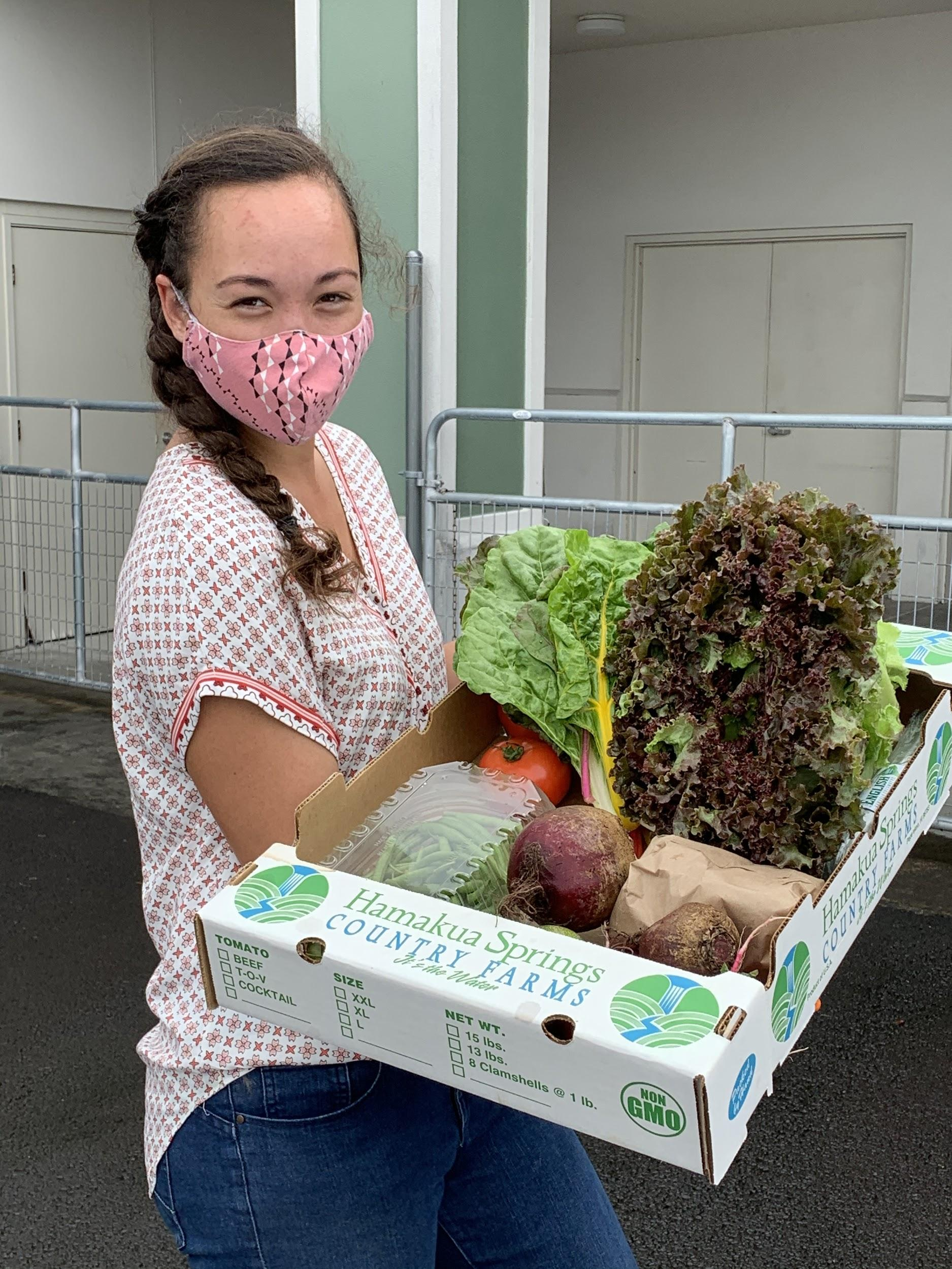 Girl holding CSA Produce Box full of vegetables